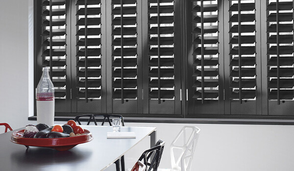 Grey wooden shutters in dining room