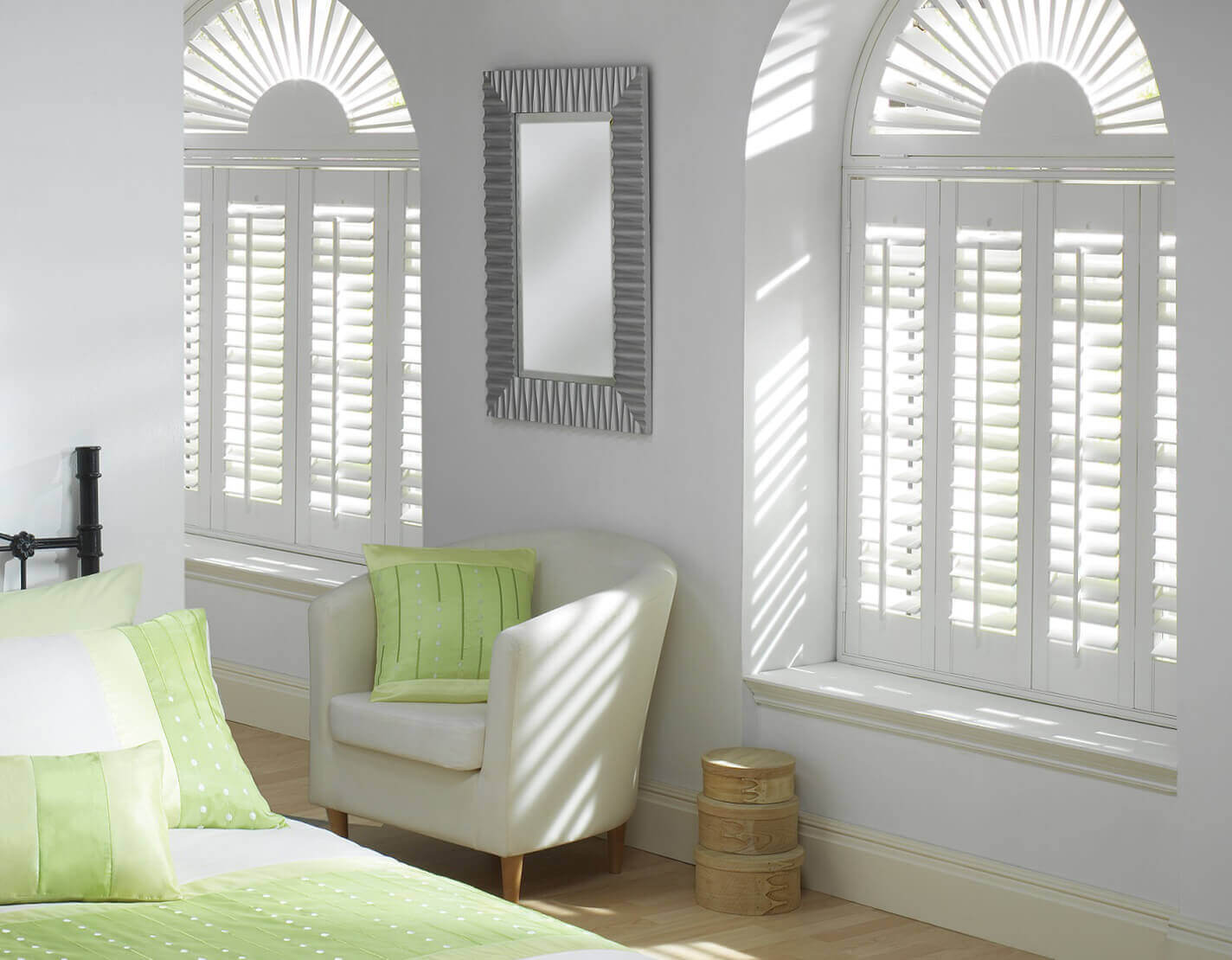 White wooden shutters angling sunlight in bedroom